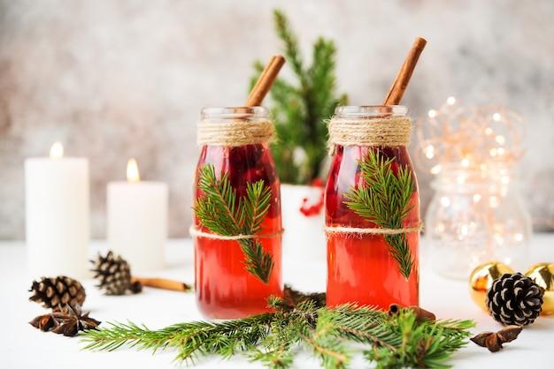 Due bottiglie di vin brulè caldo con bacche e spezie sono sul bianco con luci natalizie e decorazioni natalizie.
