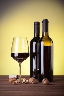 Due bottiglie di vino rosso italiano un bicchiere e noci su un tavolo di legno