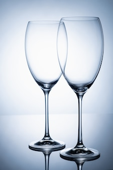Due calici di vetro senza vino su una gamba sottile si trovano su una superficie a specchio.