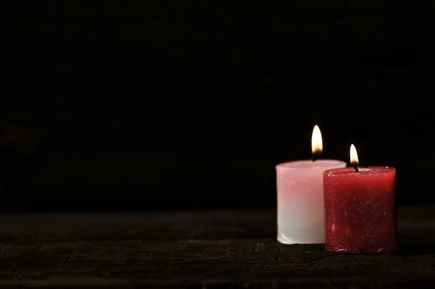 Due candele con fuoco acceso su sfondo nero