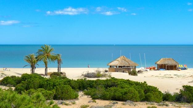 Due capanne sulla spiaggia di sabbia bianca dove i surfisti tengono le loro attrezzature