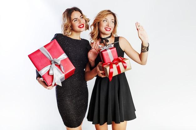 Due carino donna che celebra tenendo grandi contenitori di regalo del nuovo anno. volti a sorpresa. indossare un abito nero elegante.