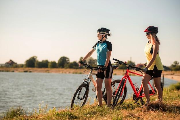 Due ciclisti donne con bici in piedi e parlando in riva al lago