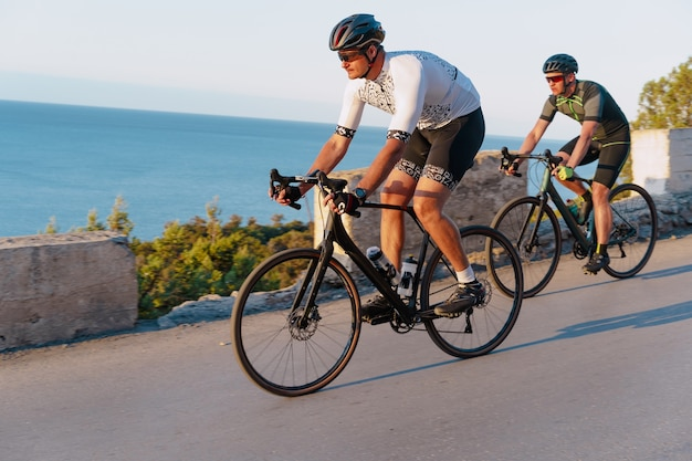 Due ciclisti maschi professionisti che guidano le loro biciclette da corsa al mattino insieme sulla strada costiera