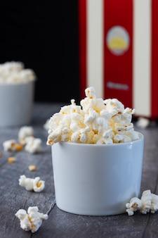 Due ciotole bianche con popcorn su un legno blu.