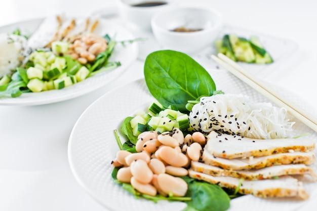 Due ciotole di cibo salutare, pasta di vetro, fagioli, petto di pollo, spinaci, rucola e cetriolo