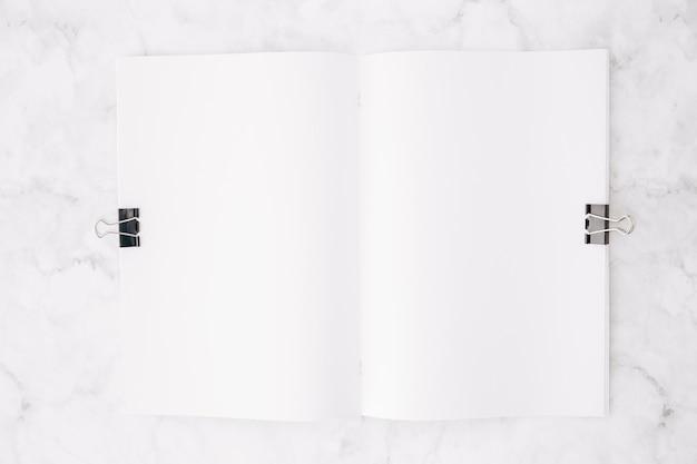 Due clip del bulldog su libro bianco sopra il contesto strutturato di marmo