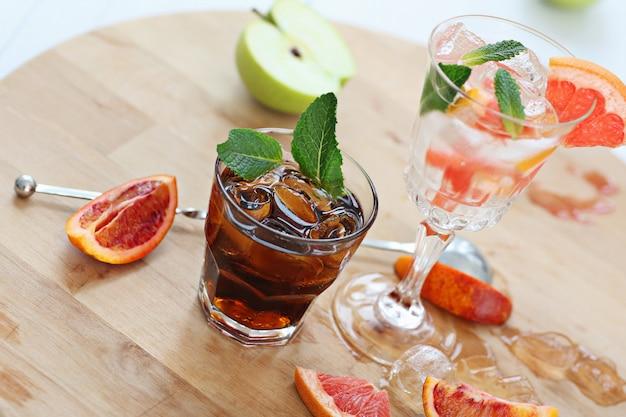 Due cocktail di whisky con cola e pompelmo con vodka di ghiaccio e menta. su una tavola di legno vengono lanciati frammenti di frutta. foto con profondità di campo.