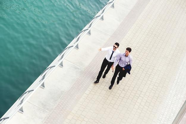 Due colleghi che camminano lungo la passeggiata del fiume. discutere di importanti argomenti commerciali nel loro cammino verso l'ufficio.
