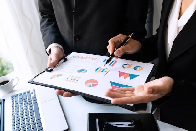 Due colleghi che discutono di dati sul tavolo scrivania in ufficio. chiuda sull'analisi del gruppo di affari e sul concetto di strategia.
