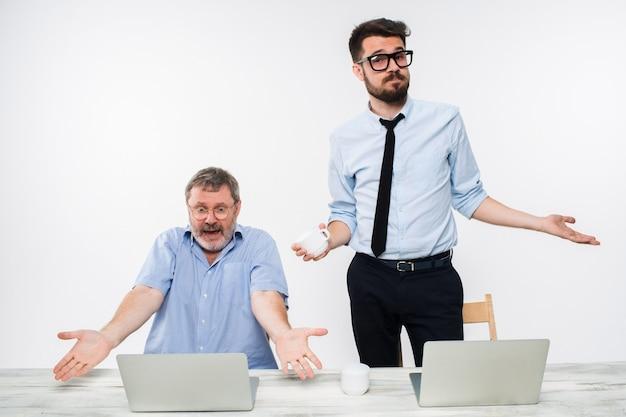 Due colleghi che lavorano insieme in ufficio su bianco