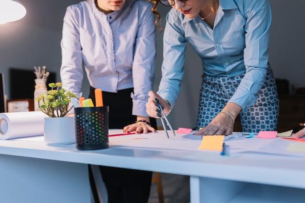 Due colleghi di sesso femminile utilizzando la bussola per fare una tabella di piani