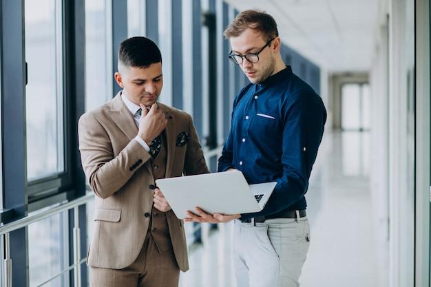 Due colleghi di sesso maschile in ufficio, in piedi con il portatile