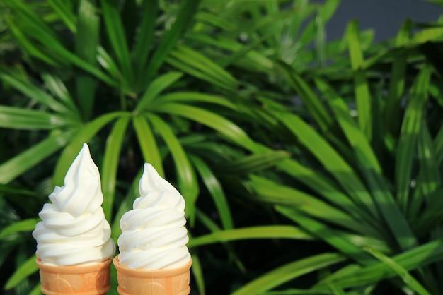 Due coni di gelato al latte morbido servire alla luce del sole con fogliame verde sfocato sullo sfondo