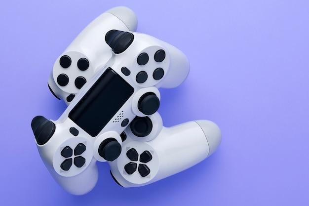 Due controller di gioco bianco isolato su sfondo viola con spazio di copia.
