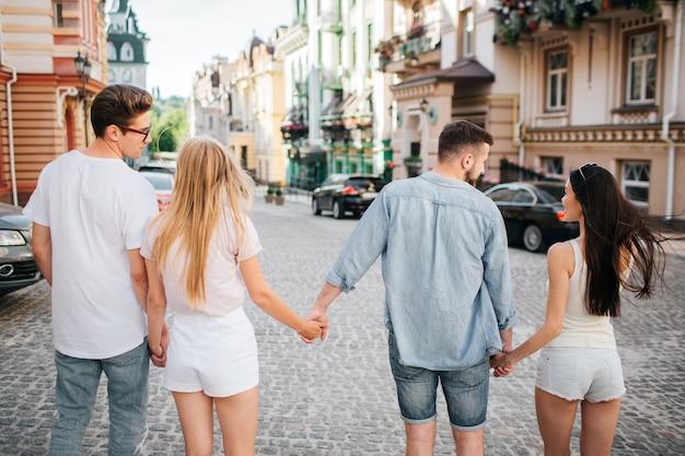 Due coppie camminano insieme lungo la strada e si tengono per mano