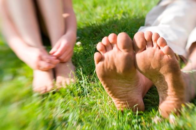 Due coppie di piedi sporchi e nudi