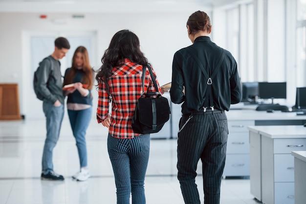 Due coppie. gruppo di giovani che camminano in ufficio durante la pausa