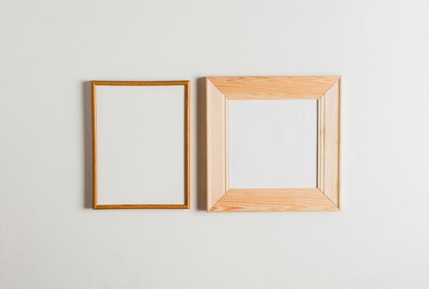 Due cornici di legno appesa al muro bianco