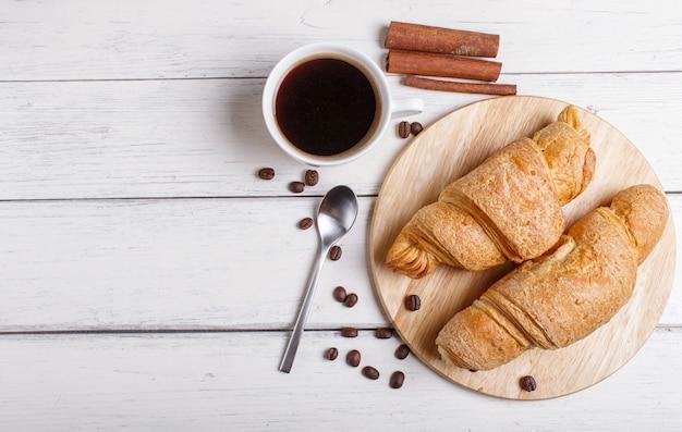 Due croissant con la tazza di caffè sul bordo di legno della cucina su fondo di legno bianco