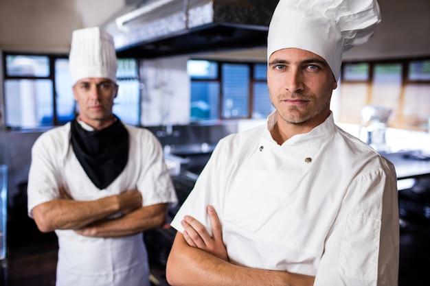 Due cuochi unici maschii che stanno con le armi hanno attraversato in cucina
