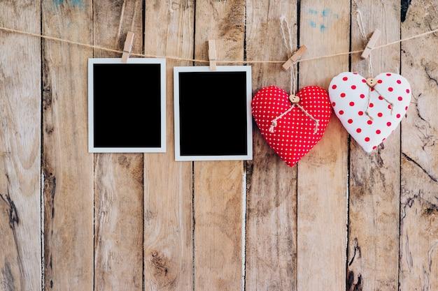 Due cuore e due cornice fotografica appesa sulla corda clothesline con sfondo in legno.