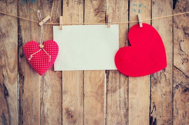 Due cuori appesi e carta su clothesline e corda con sfondo in legno