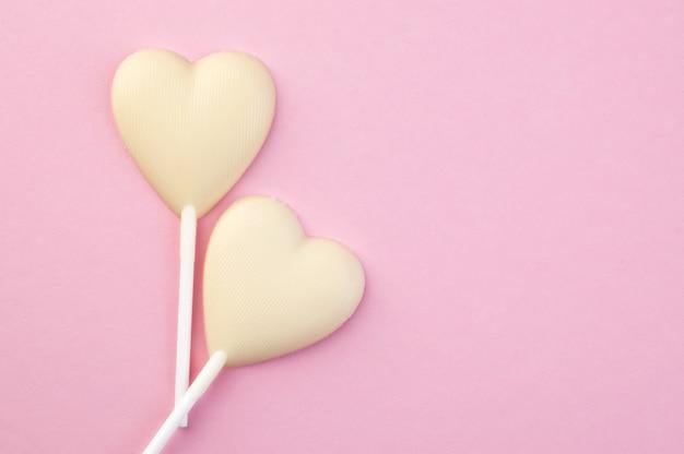 Due cuori di caramella di cioccolata bianca sul rosa