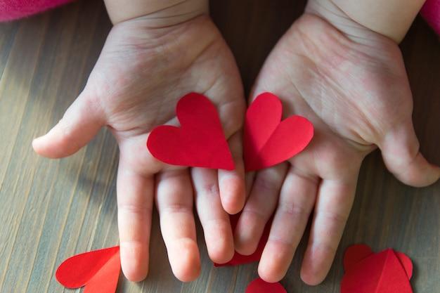 Due cuori di carta rossa nelle mani del bambino. l'amore firma dentro il giorno di biglietti di s. valentino.