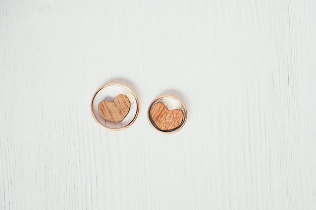 Due cuori di legno negli anelli di nozze d'oro di paia su fondo bianco. colpo di testa.