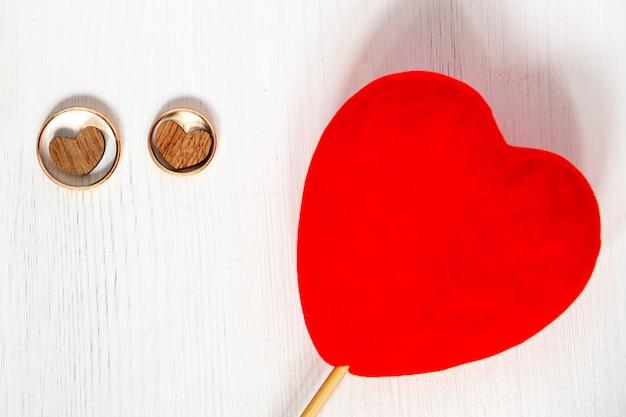 Due cuori di legno negli anelli di nozze oro coppia con cuore rosso su sfondo bianco.