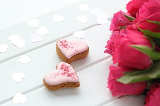 Due cuori di pan di zenzero su una superficie di legno, cuori di coriandoli e un mazzo di rose rosa brillante.
