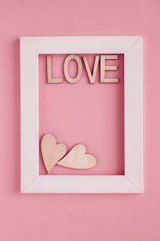 Due cuori e lettere di legno la parola amore in una cornice bianca su uno sfondo rosa