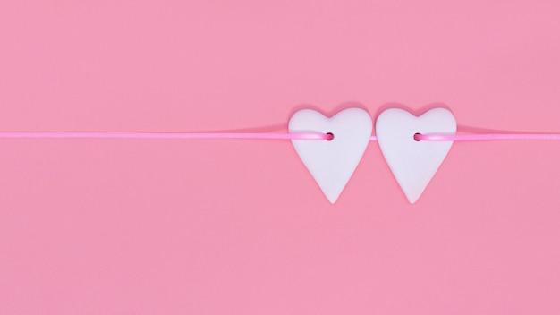 Due cuori fianco a fianco sul nastro rosa su sfondo di colore rosa pastello.