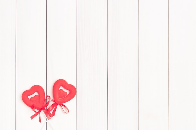 Due cuori rossi su bastoncini di legno.