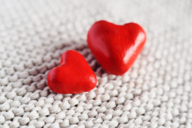 Due cuori rossi su sfondo a maglia.
