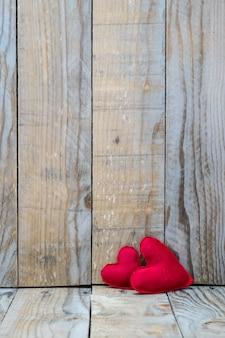 Due cuori rossi su uno sfondo in legno per san valentino