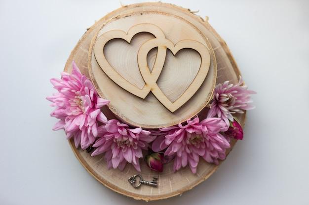 Due cuori su una fetta di legno e fiori rosa