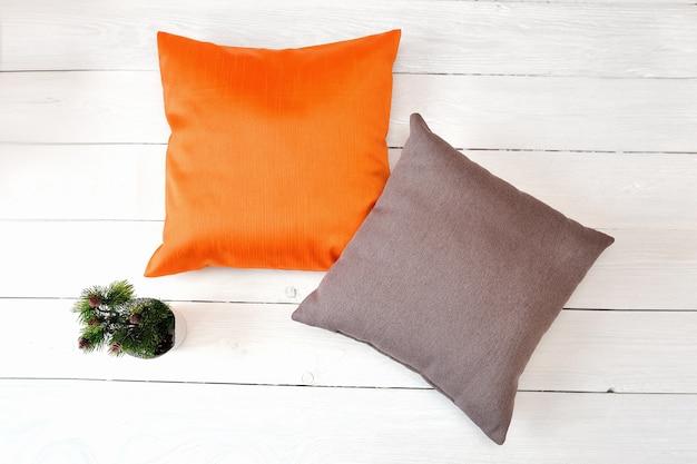 Due cuscini su uno sfondo di legno bianco. mockup di foto piatta, vista dall'alto