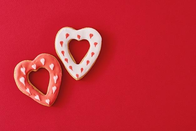 Due decorati con glassa e biscotti a forma di cuore smaltati su rosso con spazio di copia
