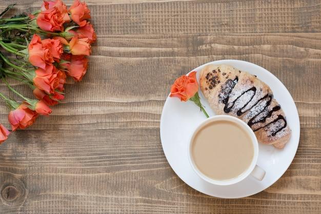Due deliziosi cornetti al cioccolato appena sfornati e tazza di caffè sul bordo di legno. vista dall'alto. concetto di colazione. copia spazio.