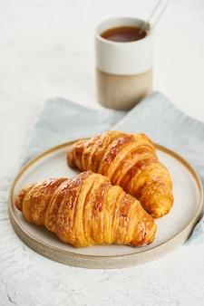 Due deliziosi cornetti sul piatto e bevanda calda in tazza. mattina colazione francese con dolci freschi