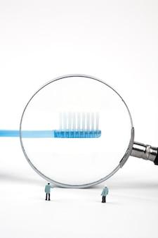 Due dentisti in miniatura che ispezionano lo spazzolino da denti con la lente d'ingrandimento