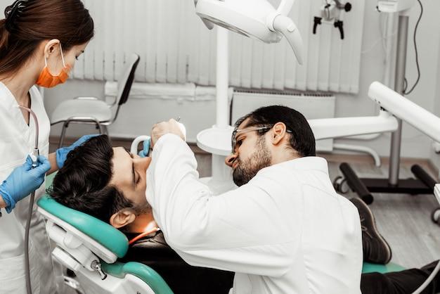 Due dentisti trattano un paziente. uniforme professionale e attrezzature di un dentista. assistenza sanitaria equipaggia il posto di lavoro di un medico. odontoiatria