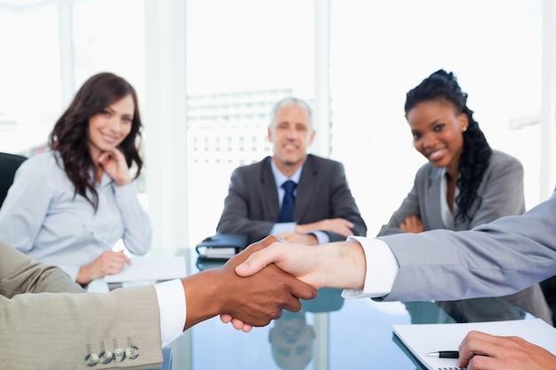 Due dirigenti si stringono la mano durante una riunione