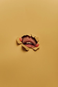 Due dita e una bocca che emerge attraverso un foro di cartone giallo
