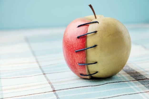 Due diverse metà della mela collegate da filo