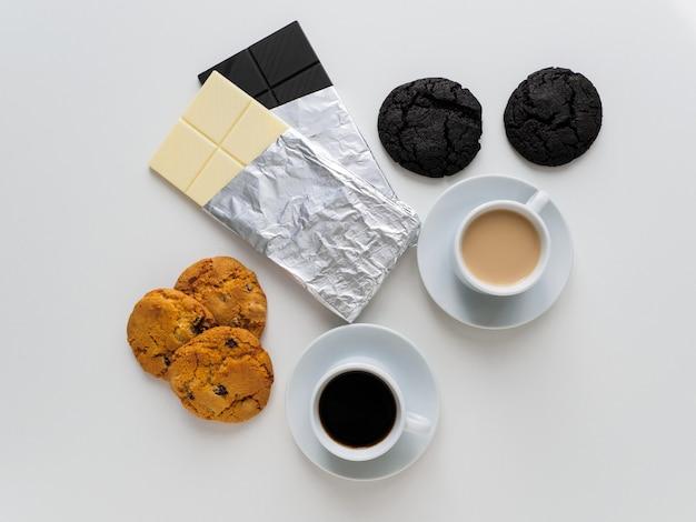 Due diverse tazze di caffè con biscotti e cioccolato