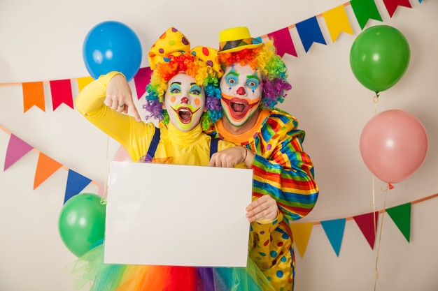 Due divertenti pagliacci alla festa tengono un cartello bianco per le iscrizioni