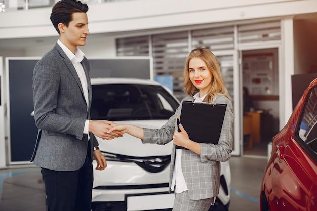 Due donna alla moda in un salone di auto